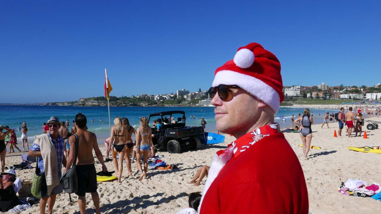 Dressed in a Santa Claus costume, a volunteer lifeguard from Lancashire, England looks out to sea from Bondi Beach, Sydney, Australia. (Image: REUTERS)