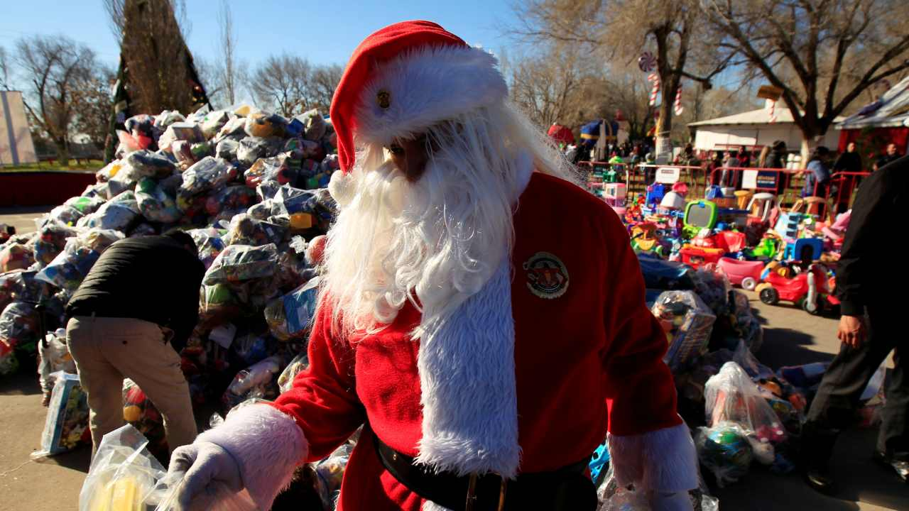 A firefighter dressed as Santa Claus is seen during the annual gift-giving event organized by the Fire Department, in which they hand out items donated throughout the year to children in need, in Ciudad Juarez, Mexico. (Image: REUTERS)