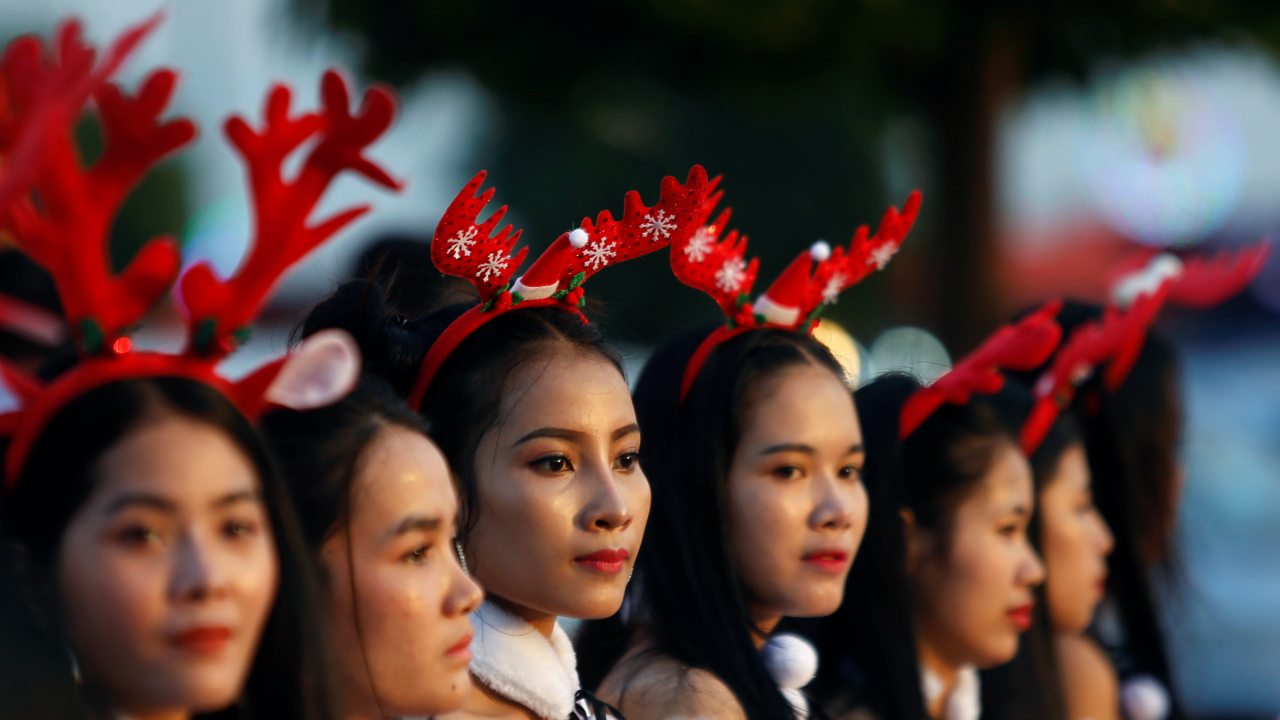 Women wearing Christmas costumes are seen along a street in Phnom Penh, Cambodia. (Image: REUTERS)