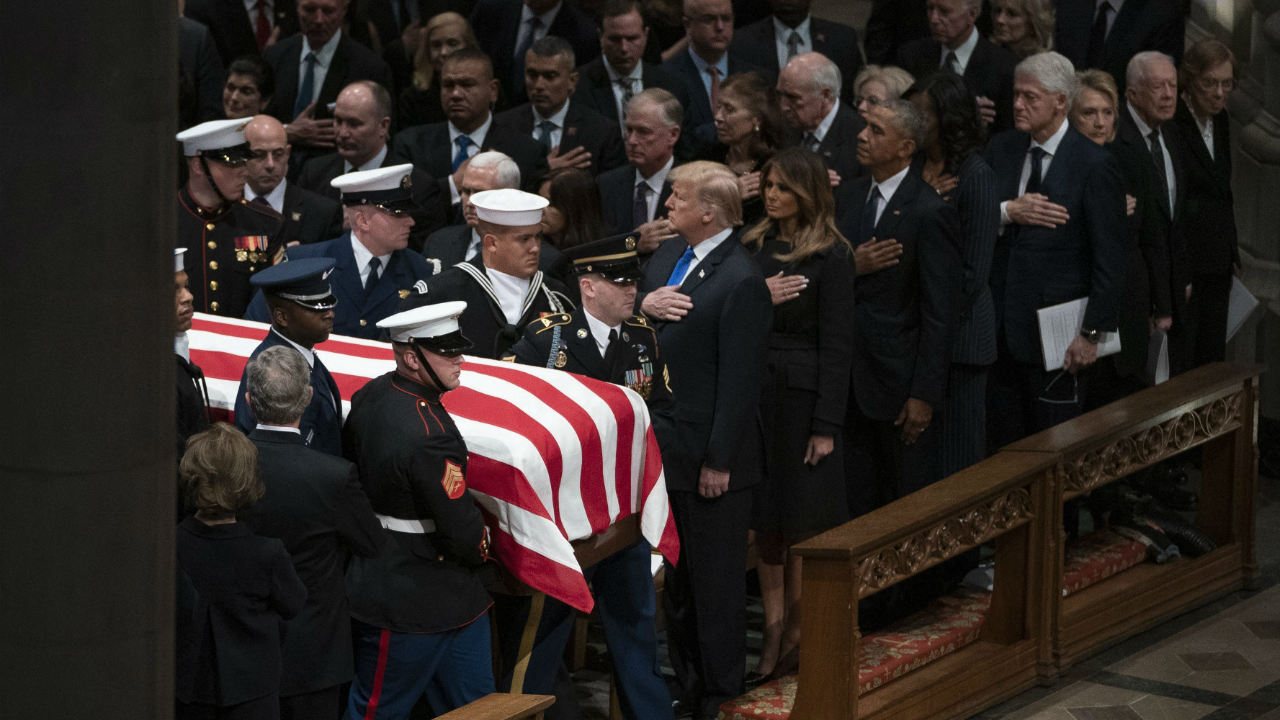 The flag-draped casket of former President George HW Bush is carried by a military honour guard past former President George W Bush and wife Laura Bush, President Donald Trump, first lady Melania Trump, former President Barack Obama, Michelle Obama, former President Bill Clinton, former Secretary of State Hillary Clinton, former President Jimmy Carter, and Rosalynn Carter during a State Funeral at the National Cathedral in Washington. (Image: AP/PTI)