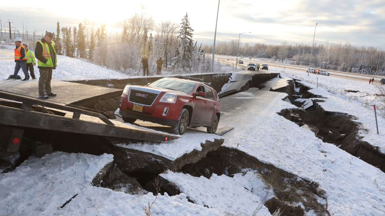 A stranded vehicle is pulled out of a collapsed section of roadway near the airport after the earthquake. (Image: Reuters)