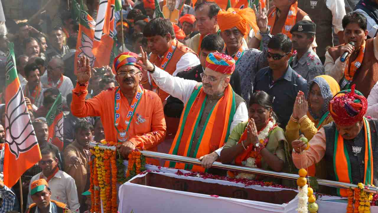 BJP President Amit Shah waves to his party supporters during a roadshow in Ajmer. (Image: PTI)