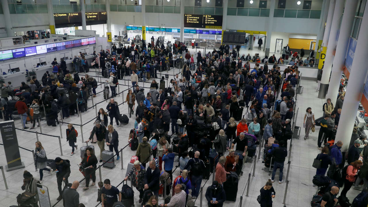 """Passengers use an escalator in Gatwick Airport, in Crawley, Britain. Full operations resumed on Saturday after British police arrested two people in connection with """"criminal use of drones"""". (Image: Reuters)"""