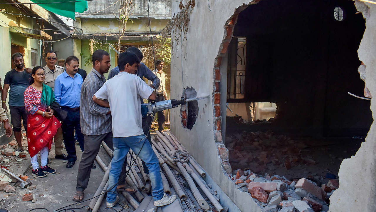 GMC workers demolish Lal Singh Mansion which was marked 'unsafe' by officials as it posed threat to life and property, in Guwahati. (Image: PTI)