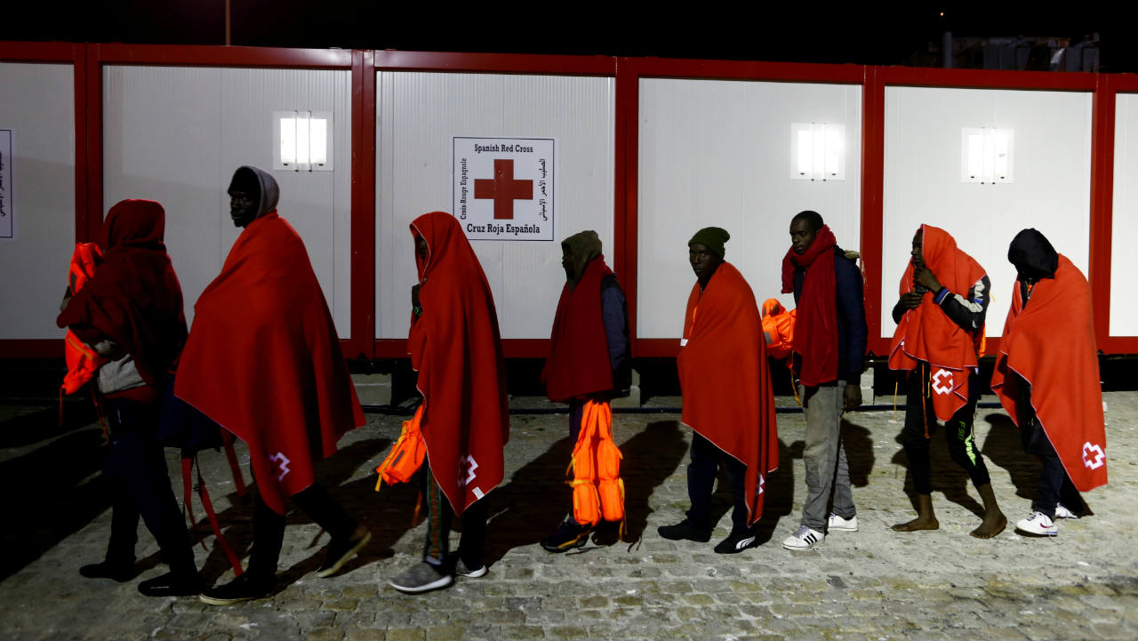 Migrants, intercepted off the coast in the Mediterranean Sea, walk after disembarking a rescue boat at the port of Malaga, southern Spain. (Image: Reuters)