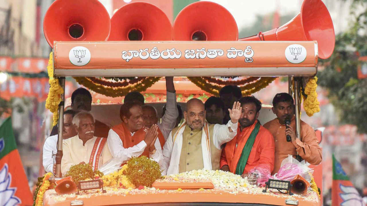BJP President Amit Shah waves at the crowd during a road show in favour of party leaders Dr K Laxman and Bandaru Dattatreya, in Musheerabad. (Image: PTI)