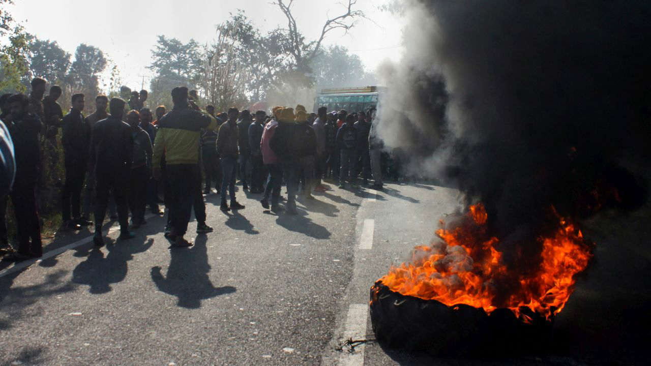 People burn tyres during a protest over alleged partiality by the polling staff in the panchayat elections at Mishriwala, at Jammu-Akhnoor highway in Jammu. (PTI)