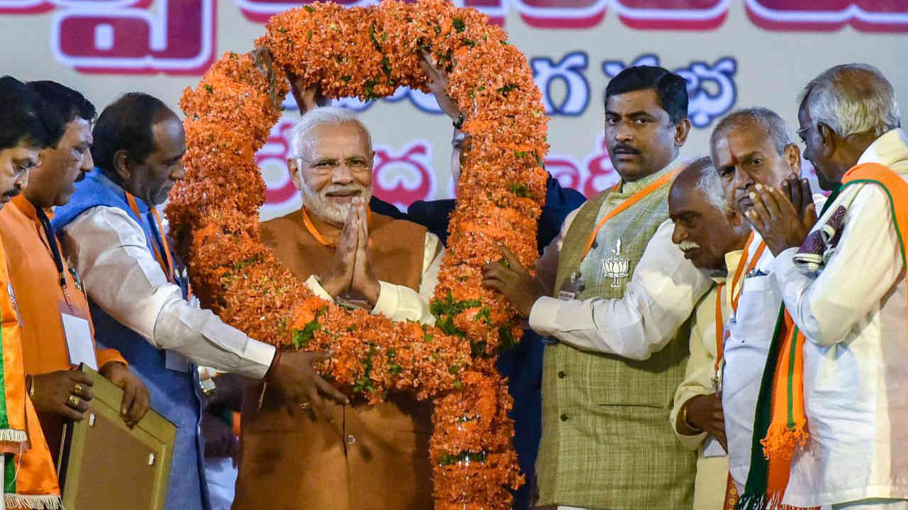 Prime Minister Narendra Modi is garlanded by Telangana party leaders during a BJP election campaign at LB Stadium, in Hyderabad. (Image: PTI)