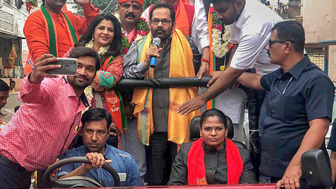 Union minister Mukhtar Abbas Naqvi, along with BJP leader Shazia Ilmi, campaigns for party candidates in Hyderabad. (Image: PTI)