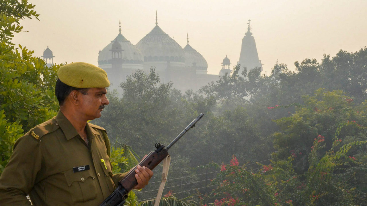 A security personnel stands guard near Shahi Idgah and Krishna Janmabhoomi Temple on the 26th anniversary of Babri mosque demolition in Mathura, Uttar Pradesh. The Ramjanmbhoomi-Babri Masjid title suit is pending in the Supreme Court, which will decide the schedule of hearing in January. (Image: PTI)