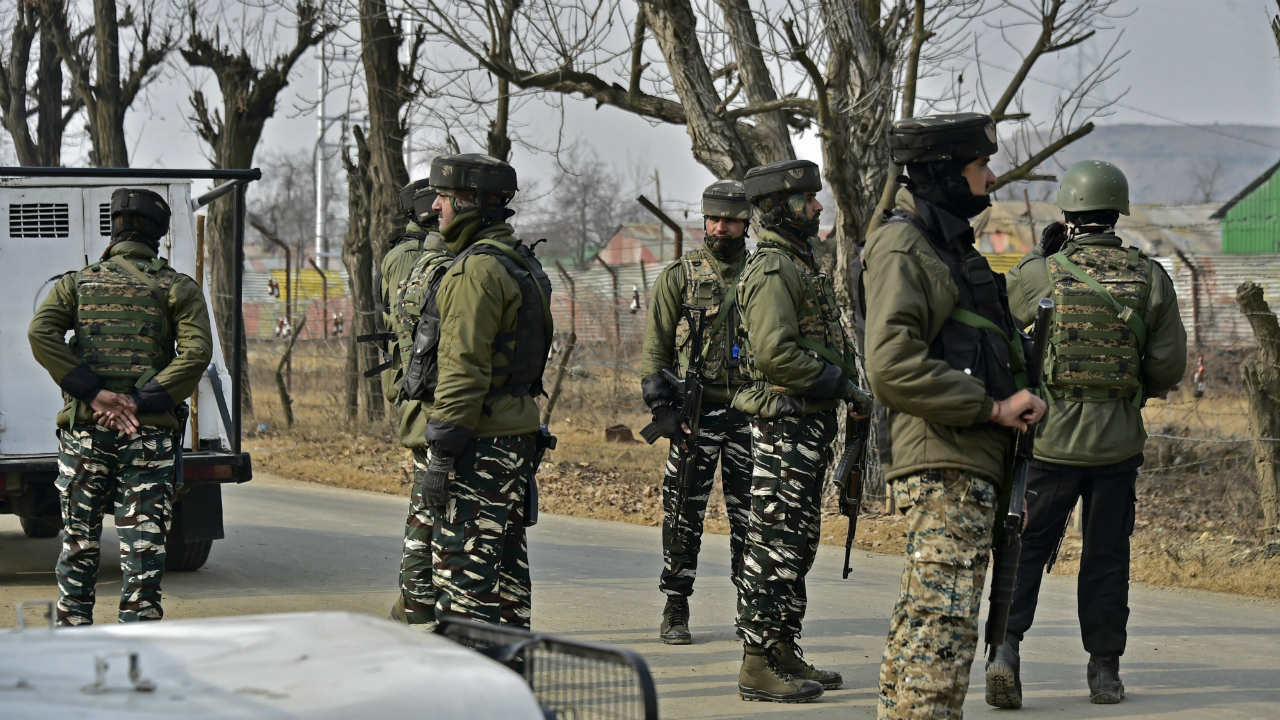 Security personnel stand guard outside an army camp where bodies of six militants of Ansar-ul-Ghazwat- ul- Hind, killed in an encounter with army, are kept for identification at Trall, in Pulwama. (Image: PTI)