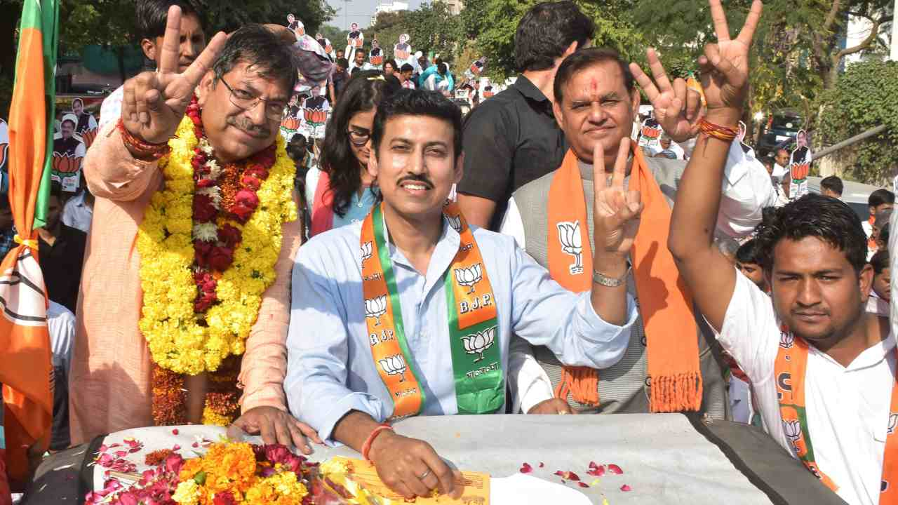 Union Minister Rajyavardhan Singh Rathore with senior BJP leader Satish Poonia, who filed his nomination papers for Amer assembly seat, in Jaipur. (Image: PTI)