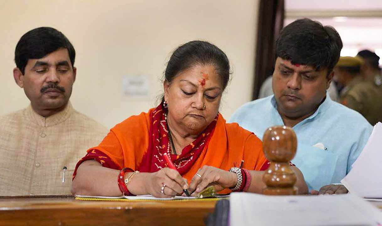 Chief Minister Vasundhara Raje, accompanied by BJP MPs Dushyant Singh and Syed Shahnawaz Hussain, files her nomination papers at Jhalawar Secretariat. (Image: PTI)