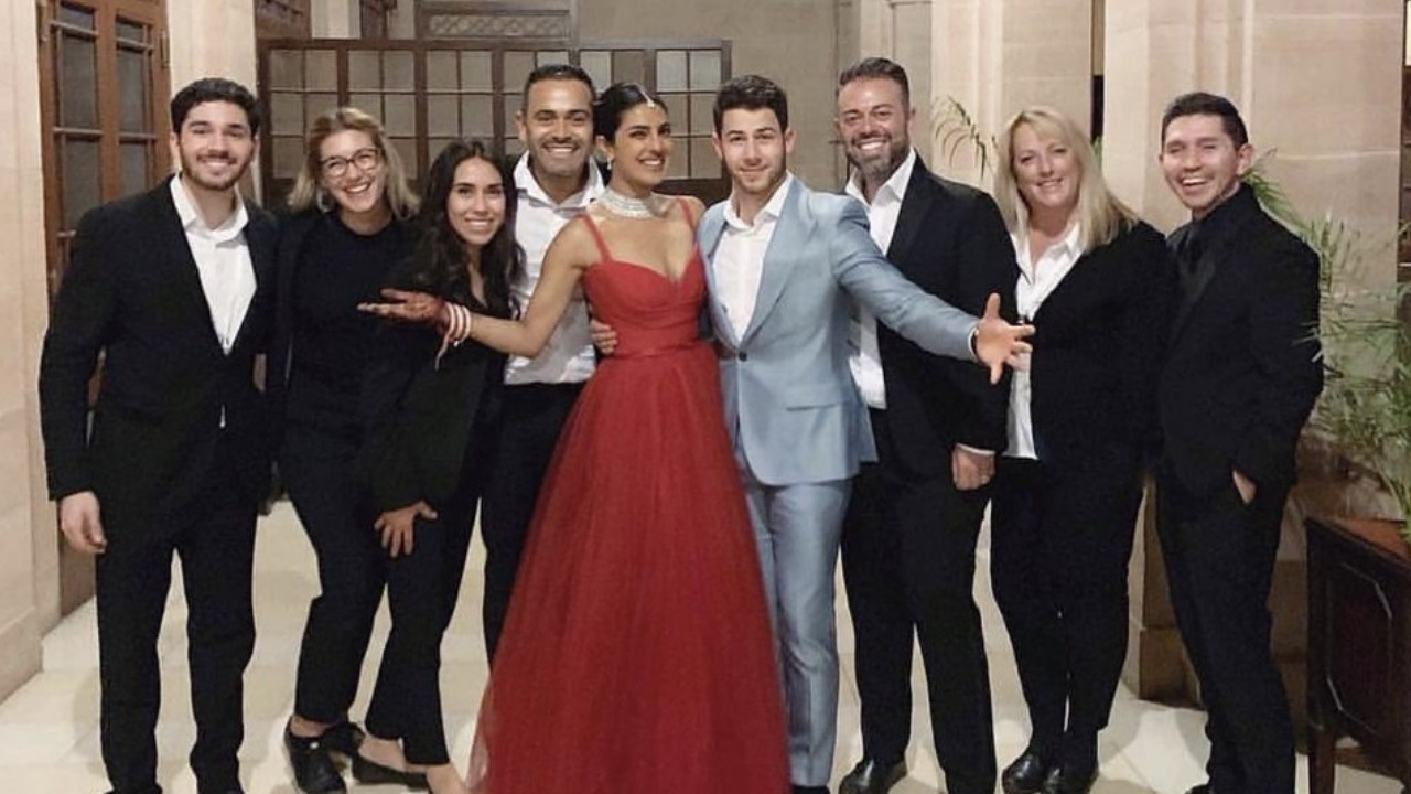 Priyanka Chopra sports a red gown as she stands next to husband Nick Jonas at their Umaid Bhawan reception. (Image: @PriyankaCentral)