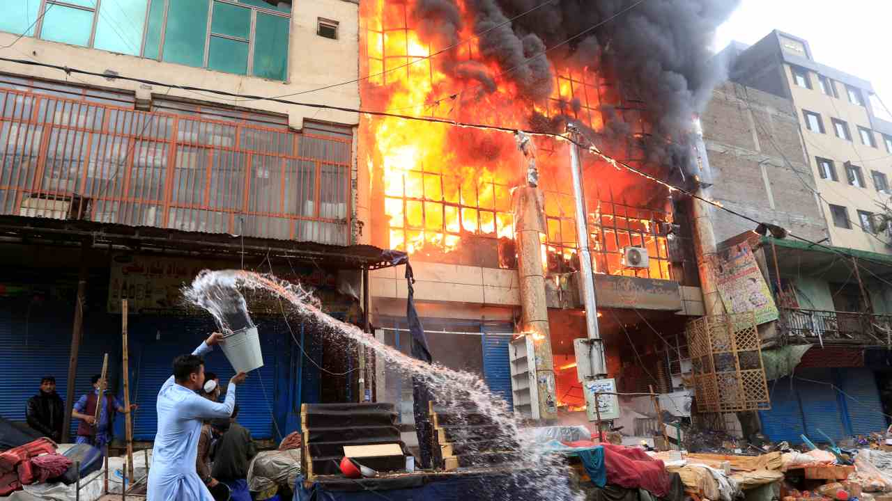 An Afghan man pours water to extinguish a fire at a commercial market in Jalalabad, Afghanistan. (Image: Reuters)