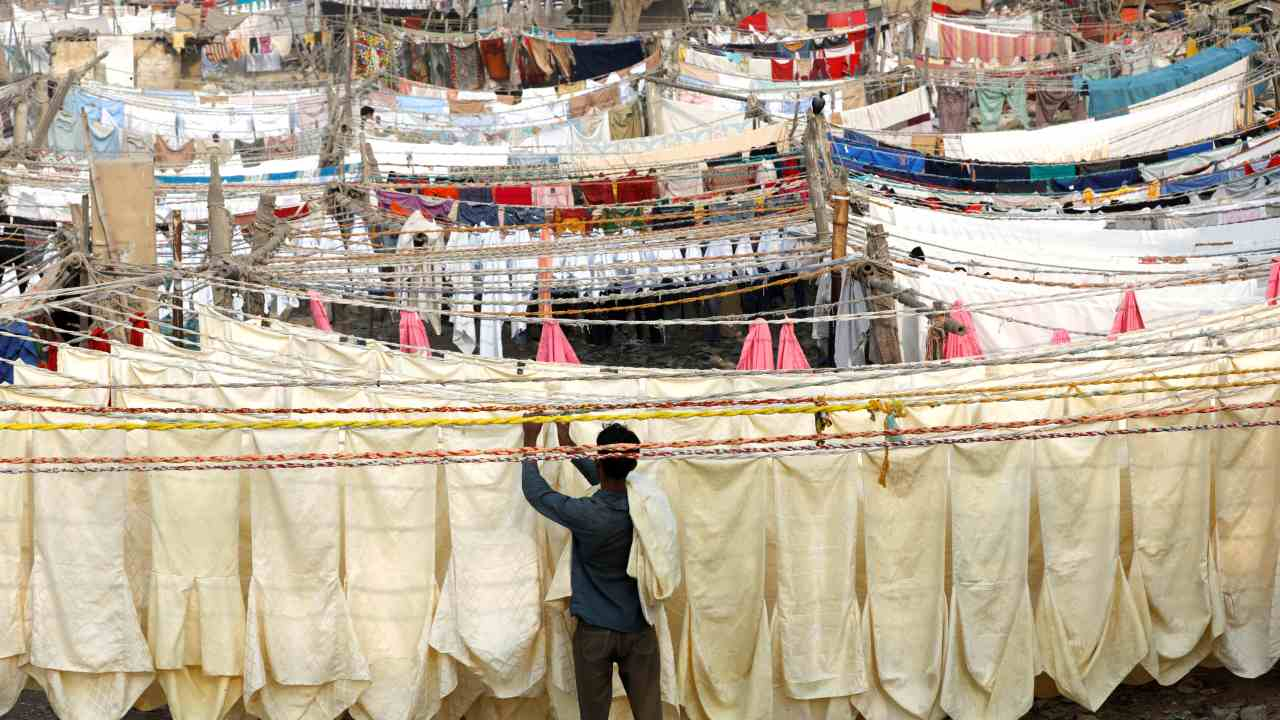 A laundry man removes chair covers from a rope after a wash and dry at a Dhobi Ghat (washing place) in Karachi, Pakistan. (Image: Reuters)