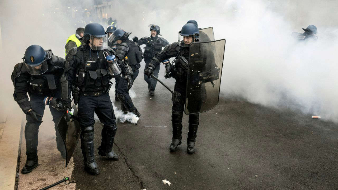 French riot police take position in a cloud of tear gas during clashes with yellow vest protesters in Lyon, central France. Authorities deployed thousands of security forces nationwide for a ninth straight weekend of anti-government protests. (AP/PTI)