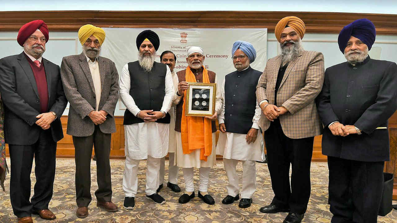 Prime Minister Narendra Modi releases a commemorative coin to mark the birth anniversary of Guru Gobind Singh Ji, the tenth guru of Sikhs, in New Delhi. Former prime minister Manmohan Singh, MoS for Housing and Urban Affairs (I/C) Hardeep Singh Puri and others are also seen. (PTI)