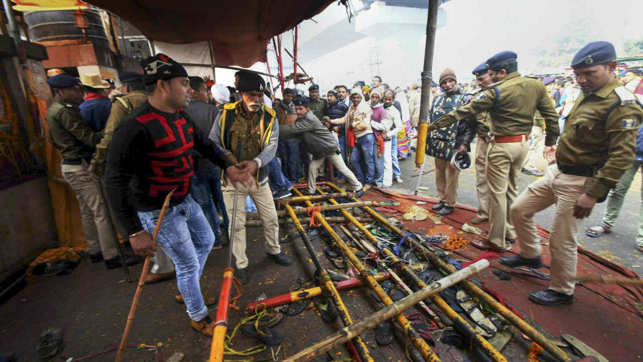 Police personnel look at the footwear of the devotees left after a stampede on the first day of the new year 2019 at historical Sankat Mochan temple (Mahavir Mandir) in Patna. (Image: PTI)