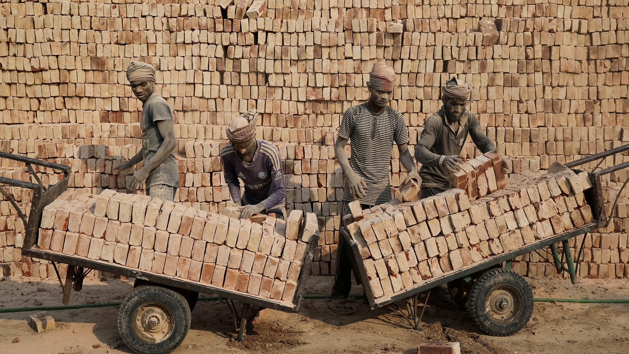 Brick factory workers stack bricks on carts in Dhaka. (Image: Reuters)