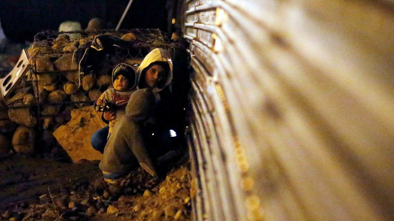 Migrants from Honduras, part of a caravan of thousands from Central America trying to reach the United States, sit near the border fence to cross it illegally from Mexico into the US, in Tijuana, Mexico. (Reuters)