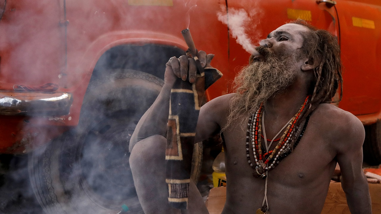"A Naga Sadhu smokes outside his tent ahead of the ""Kumbh Mela"" in Prayagraj. (Image: Reuters)"