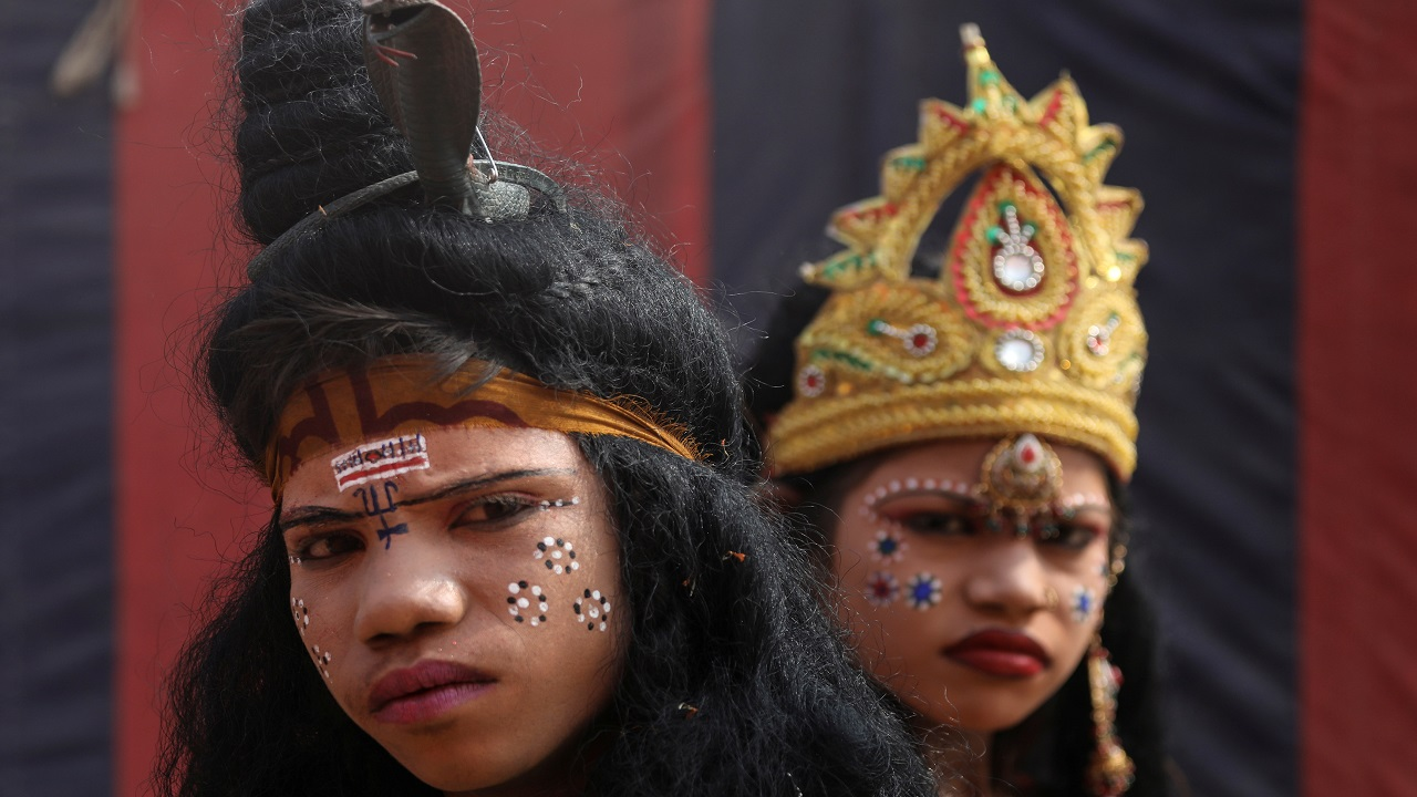 "Children, dressed up as a Hindu God and Goddess, look on as they beg for alms during ""Kumbh Mela""in Prayagraj. (Image: Reuters)"