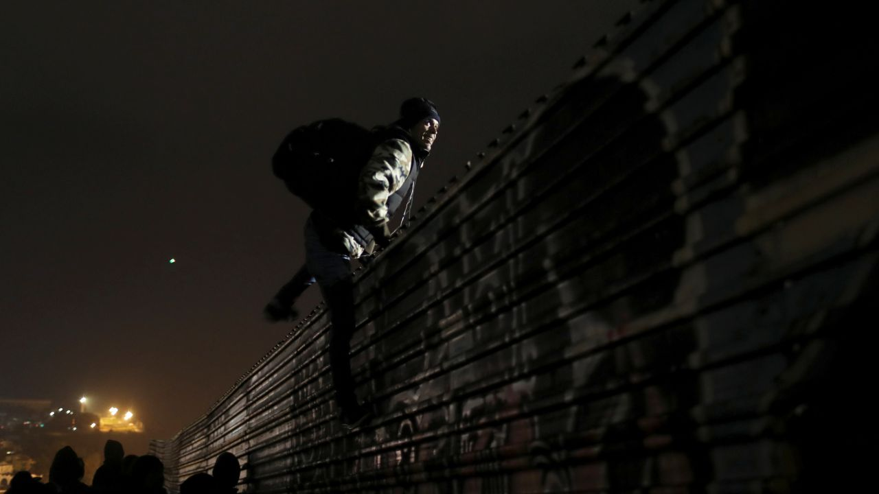 A migrant from Honduras, part of a caravan of thousands from Central America trying to reach the United States, jumps a border fence to cross illegally from Mexico into the US, in Tijuana, Mexico. (Image: Reuters)