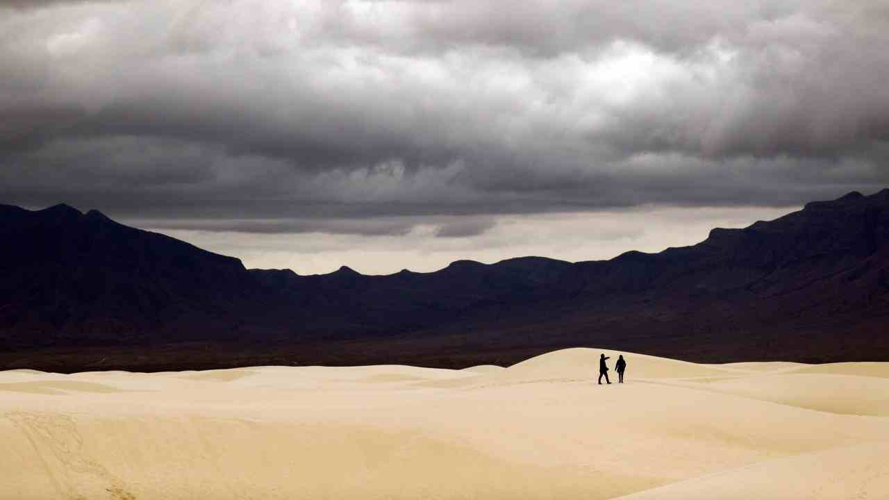 Visitors walk across dunes at White Sands National Monument as a rain storm passes near Alamogordo, New Mexico. (AP/PTI)
