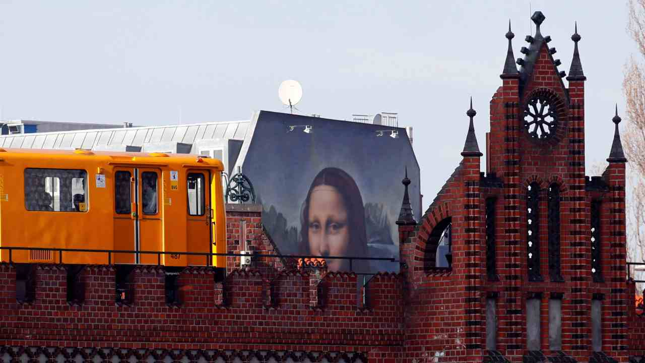 """A U-Bahn underground train passes by a mural by Berlin-based street art gang """"Die Dixons"""" (The Dixons) which features a giant reproduction of Leonardo da Vinci's artwork Mona Lisa, near East Side Gallery, Germany. (Image: Reuters)"""