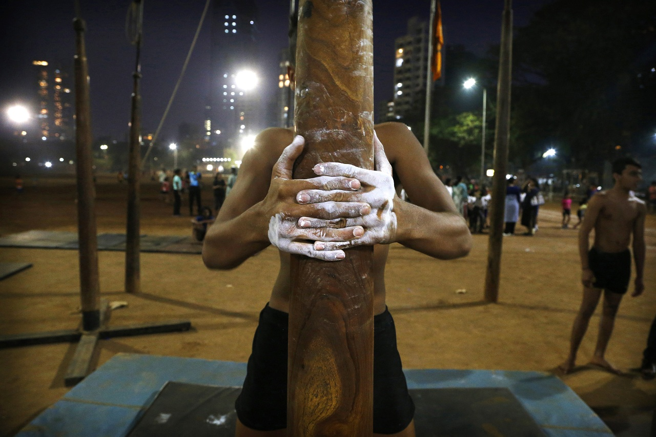 In this Feb. 4, 2019, photo, a player tightens his grip on a mallakhamb pole as he trains at Shivaji Park in Mumbai, India. The word mallakhamb comes from malla, meaning wrestler, and khamb, or pole, and is a traditional training exercise for wrestlers in India. After centuries of being practiced in isolation in the subcontinent, mallakhamb is set to have its first international championship in Mumbai on Feb. 16 and 17. (AP Photo/Rafiq Maqbool)
