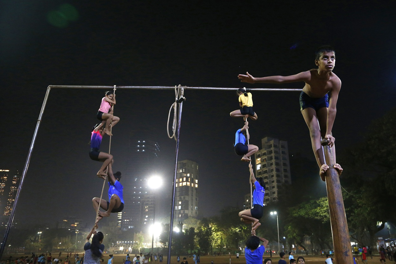 In this Feb. 4, 2019, photo, players perform on a mallakhamb pole and rope at the Shree Samartha Vyayam Mandir at Shivaji Park in Mumbai, India. The word mallakhamb comes from malla, meaning wrestler, and khamb, or pole, and is a traditional training exercise for wrestlers in India. After centuries of being practiced in isolation in the subcontinent, mallakhamb is set to have its first international championship in Mumbai on Feb. 16 and 17. (AP Photo/Rafiq Maqbool)