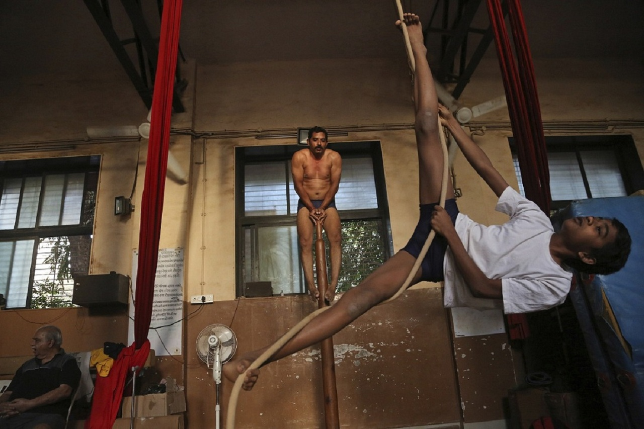 In this Feb 5, 2019, photo, mallakhamb players perform on a pole and rope at the Shree Samartha Vyayam Mandir at Shivaji Park in Mumbai, India. The word mallakhamb comes from malla, meaning wrestler, and khamb, or pole, and is a traditional training exercise for wrestlers in India. After centuries of being practiced in isolation in the subcontinent, mallakhamb is set to have its first international championship in Mumbai on Feb. 16 and 17. (AP Photo/Rafiq Maqbool)