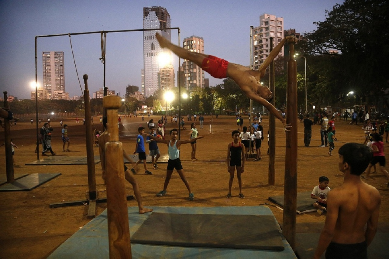 In this Feb 6, 2019, photo, a player performs on a mallakhamb pole as he trains at Shivaji Park in Mumbai, India. The word mallakhamb comes from malla, meaning wrestler, and khamb, or pole, and is a traditional training exercise for wrestlers in India. After centuries of being practiced in isolation in the subcontinent, mallakhamb is set to have its first international championship in Mumbai on Feb. 16 and 17. (AP Photo/Rafiq Maqbool)