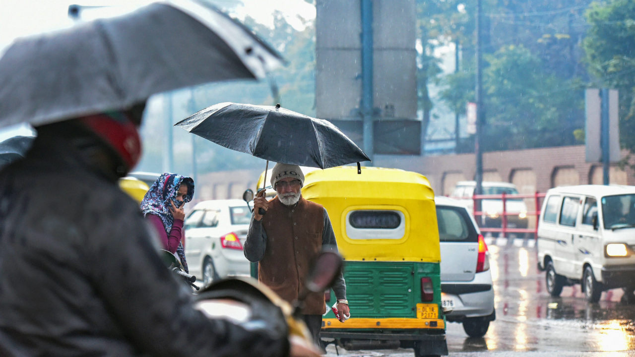Pedestrians carry umbrellas during rain on a cold morning, in New Delhi. (Image: PTI)