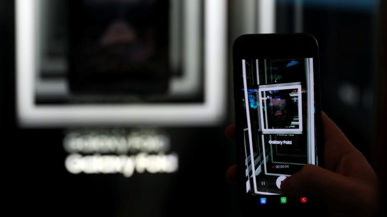A man films the new Samsung Galaxy Fold device inside the Samsung booth at the Mobile World Congress in Barcelona, Spain, February 26, 2019. REUTERS/Sergio Perez - RC1E4AE0FD00