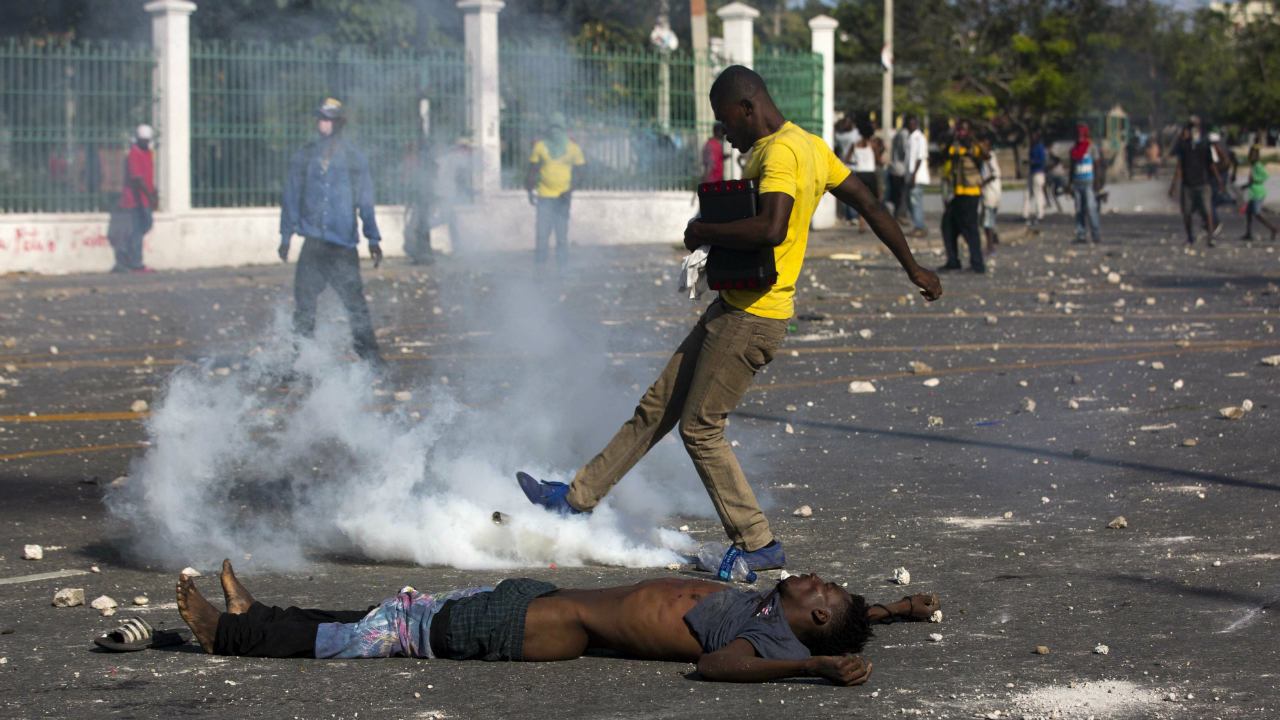 The body of an anti-government protester lies in the street outside the presidential palace, where his body was placed as a form of protest against the president, and where national police responded with tear gas during protests demanding the resignation of Haitian President Jovenel Moise near the presidential palace in Port-au-Prince. (Image: AP)
