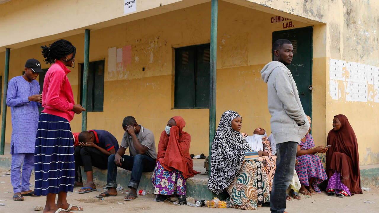 Independent National Electoral Commission (INEC) workers sit outside the Doubeli polling station, after they arrived at the unit unaware of the postponement of the presidential election in Yola, in Adamawa State, Nigeria. (Image: Reuters)