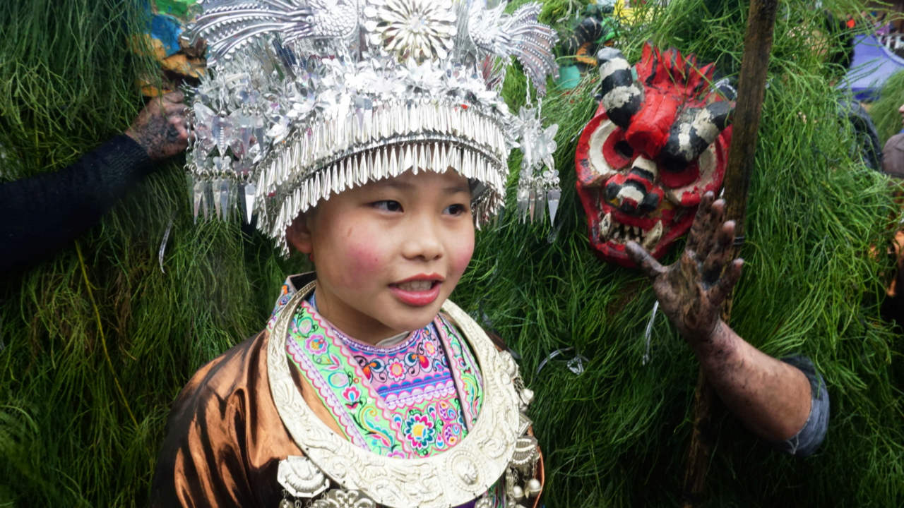 """An ethnic Miao woman poses with ethnic Miao men dressed as """"Manghao"""" during an event to celebrate the Manghao Festival at Rongshui Miao Autonomous County, in Liuzhou, Guangxi Zhuang Autonomous Region, China.(Image: Reuters)"""