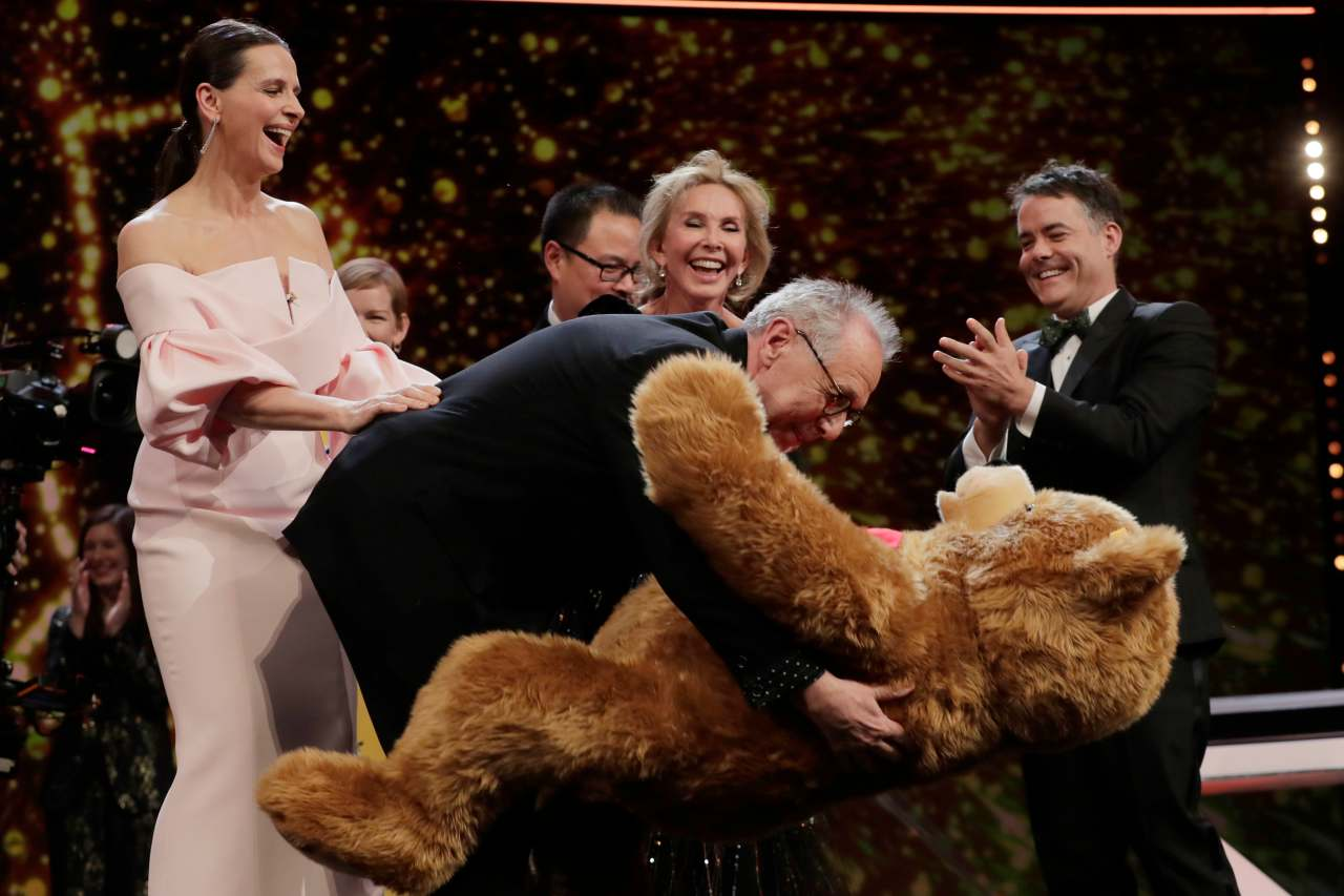Festival director Dieter Kosslick (centre) embraces a teddy bear given by jury members on the occasion of his eighteenth and final Berlinale, at the award ceremony of the 2019 Berlinale Film Festival in Berlin, Germany. (Image: AP