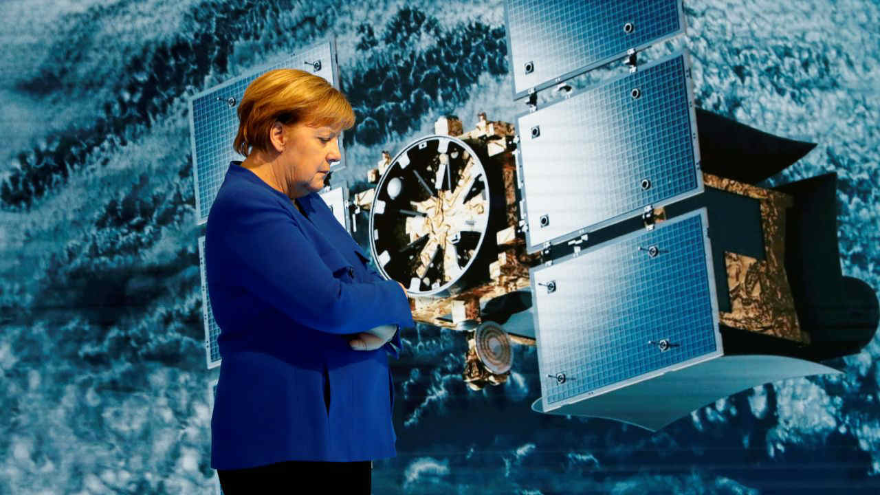 German Chancellor Angela Merkel stands in front of a large screen introducing NEC's satellite-mounted radar system for monitoring urban infrastructure and disaster prevention as she visits NEC Future Creation Hub at the headquarters of NEC in Tokyo, Japan. (Reuters)