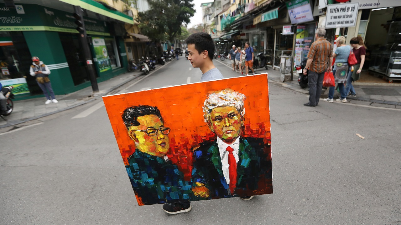 A man walks while holding a painting of Kim Jong Un and Donald Trump. (Image: Reuters)