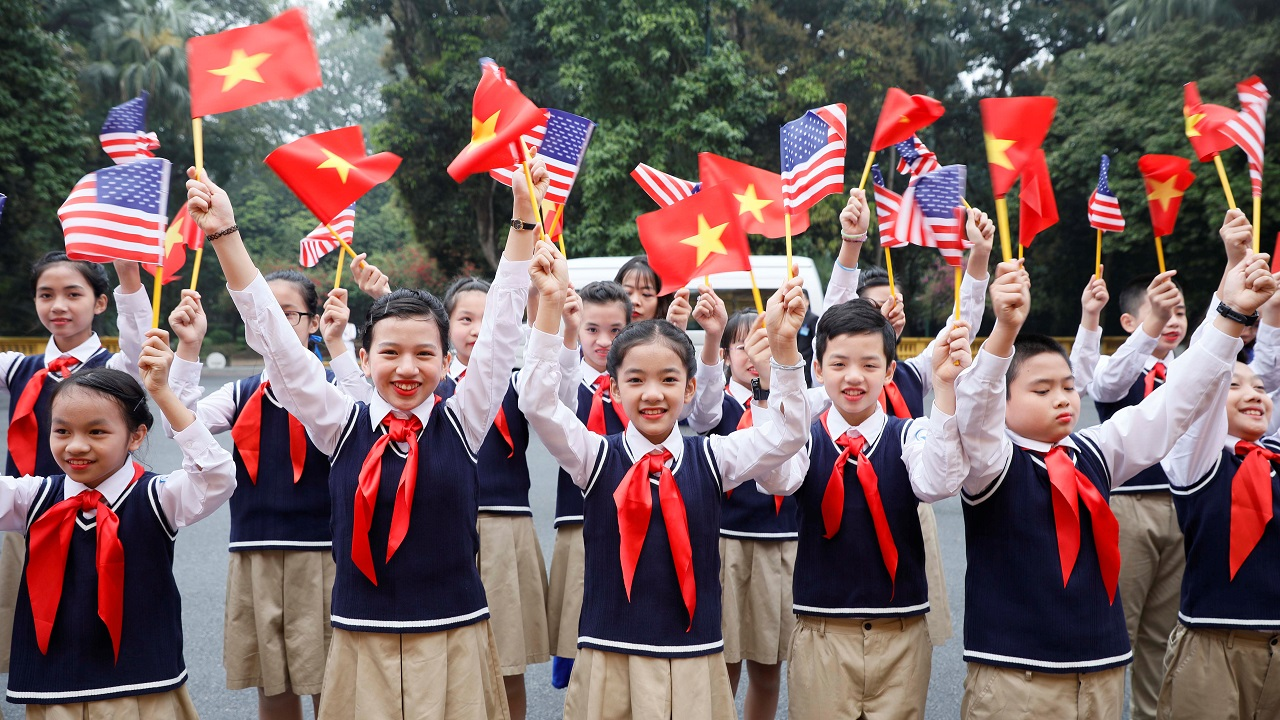 Vietnamese children wave flags of Vietnam and US before the arrival of Donald Trump at the Presidential Palace in Hanoi. (Image: Reuters)