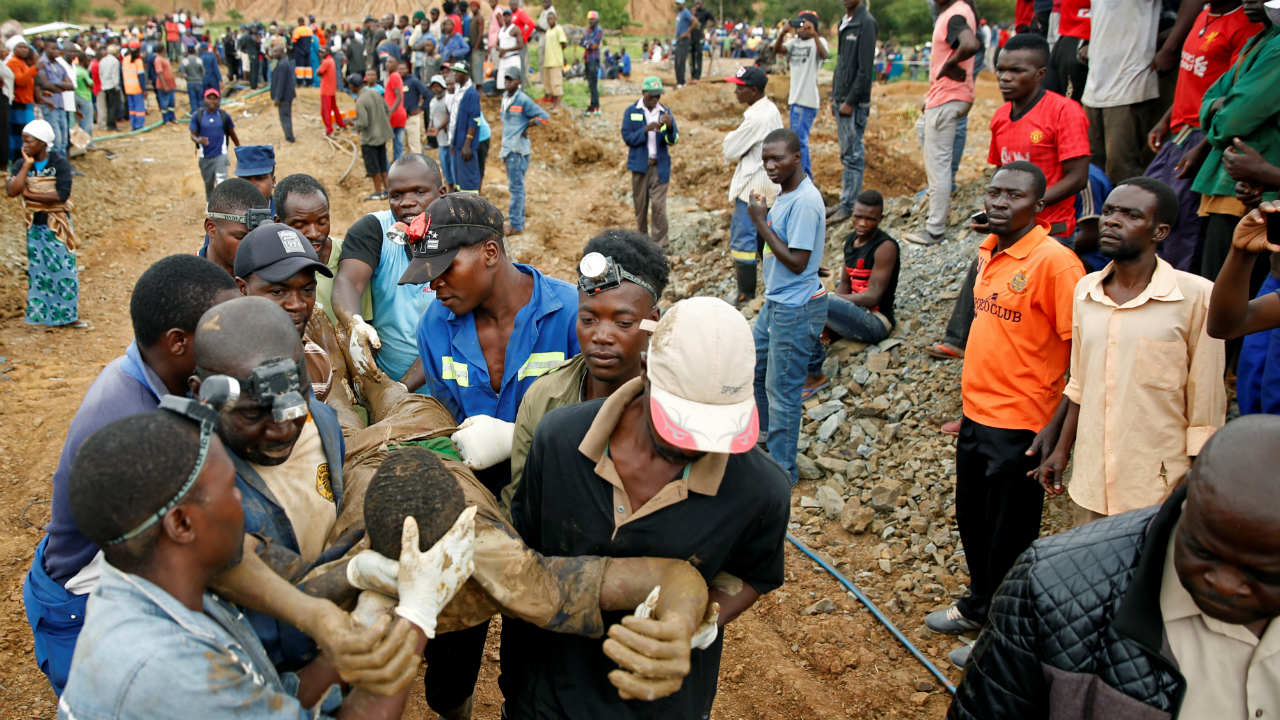 A rescued artisinal miner is carried from a pit as retrieval efforts proceed for trapped illegal gold miners in Kadoma, Zimbabwe. (Image: Reuters)
