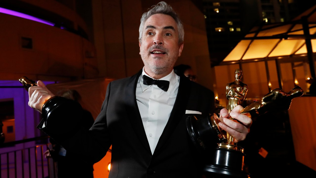 "Alfonso Cuaron of Mexico poses backstage with his Best Director, Best Foreign Language Film and Best Cinematography awards for his film ""Roma"". (Image: Reuters)"