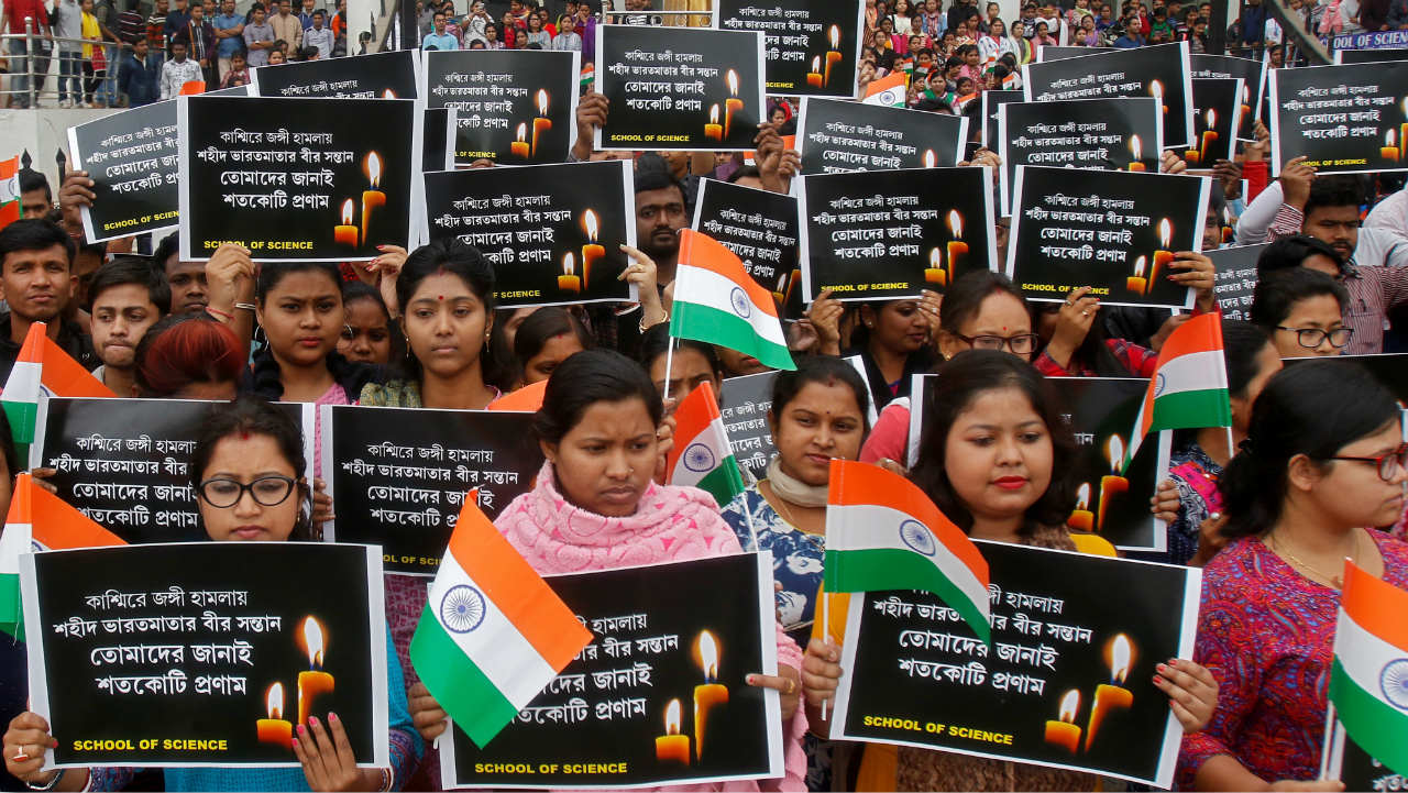 "Students hold placards during a vigil to pay tribute to Central Reserve Police Force (CRPF) personnel who were killed after a suicide bomber rammed a car into a bus in south Kashmir on Thursday, in Agartala. The placards read ""Tribute to brave sons of mother India martyred in Kashmir"". (Photo: Reuters)"