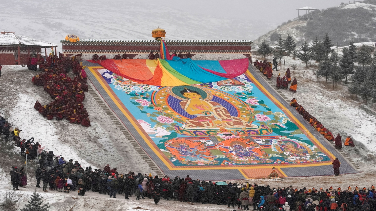 Tibetan monks unfold a giant thangka, a religious silk embroidery or painting displaying the Buddha portrait, amid snowfall at Langmu Lamasery during the Sunbathing Buddha Festival, in Gannan Tibetan Autonomous Prefecture, Gansu Province, China. (Image: Reuters)