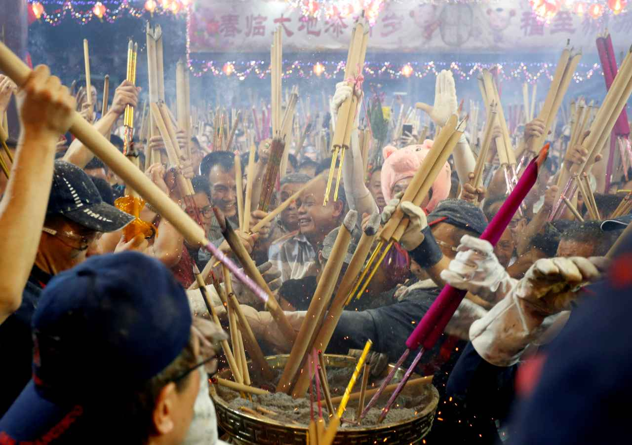 The pomp and splendour spilt on to the streets the next morning, as hundreds lined up outside famous temples to burn the first joss sticks of the year. (Image: Reuters)