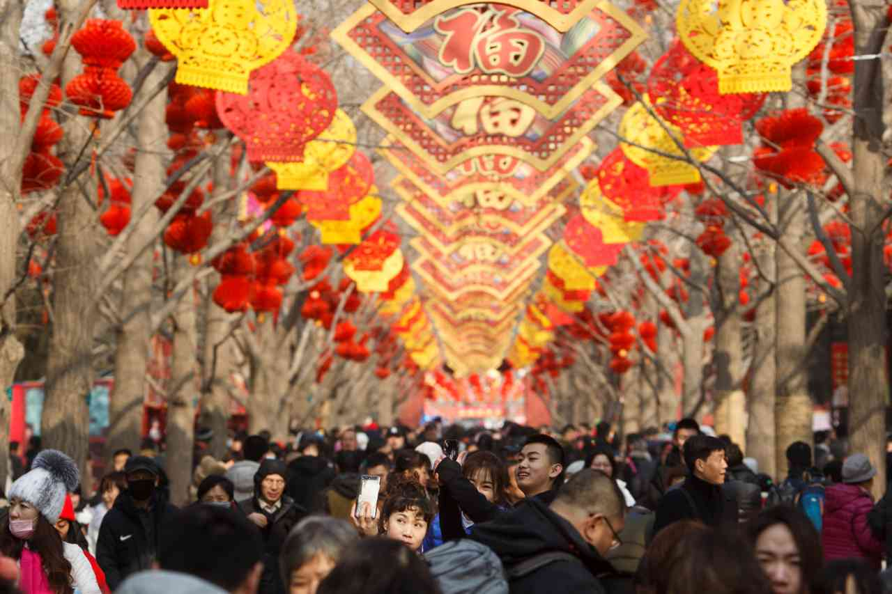 The traditional red colour adorned everything from lanterns, to clothes, to signs and pig dolls were displayed in shops and homes for the 15-day festival. (Image: Reuters)