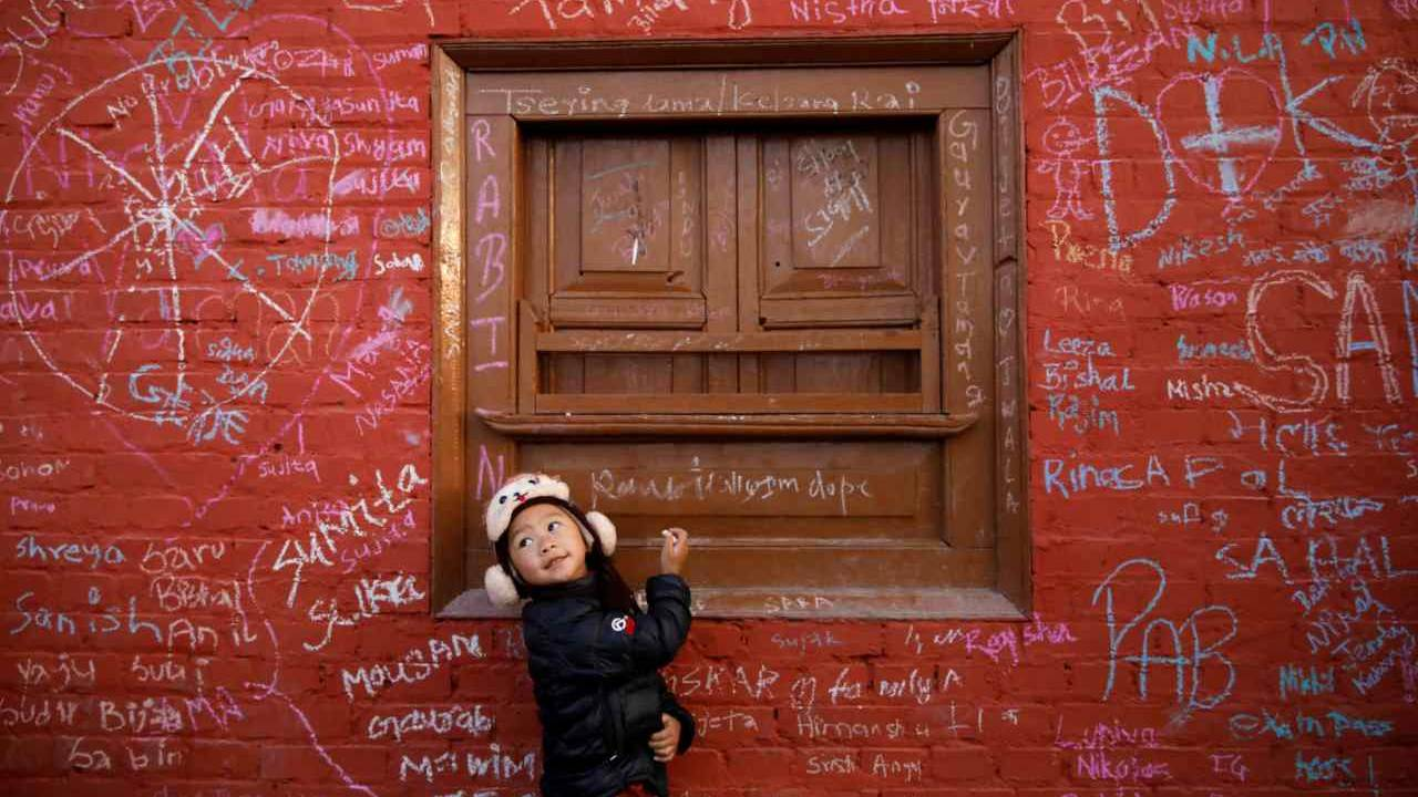 A girl looks towards her father as she writes on the wall of a Saraswati temple during the Shreepanchami festival dedicated to the goddess of education Saraswati in belief that the goddess will help devotees excel in education. (Image: Reuters)